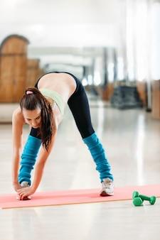 Sportlerin, die das ausrichten des trainings im fitnessstudio tut