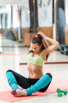 Sportlerin, die das strecken im fitnessstudio tut