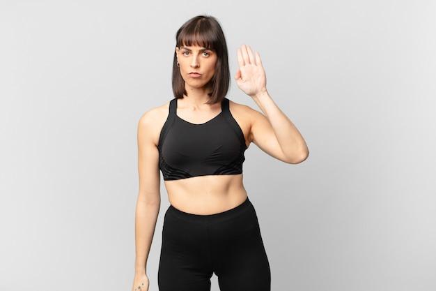 Sportlerin, die ernst, streng, unzufrieden und wütend aussieht und offene handfläche zeigt, die eine stopp-geste macht