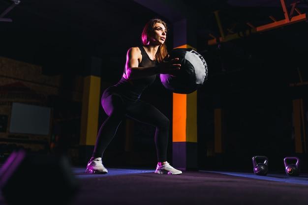Sportlerin, die hockenübungen mit eignungsball tut. frau, die mit medizinball an der turnhalle trainiert und ausdehnt