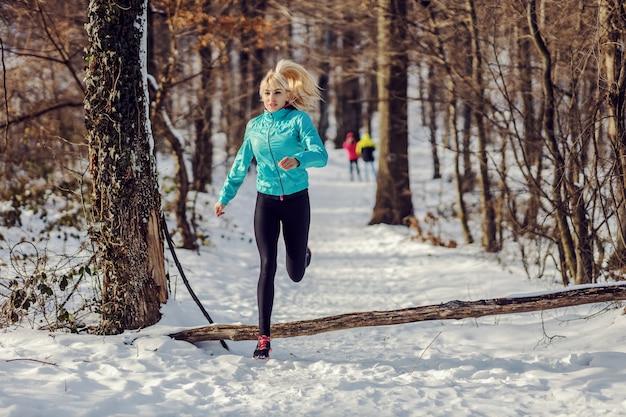 Sportlerin, die im wald am verschneiten wintertag läuft. outdoor-sport, cardio-übungen, winter-fitness