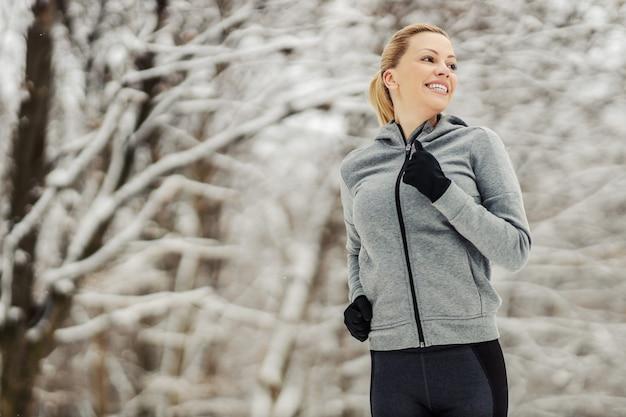 Sportlerin, die im wald läuft, ist schneebedeckter wintertag. winter fitness, gesundes leben, natur