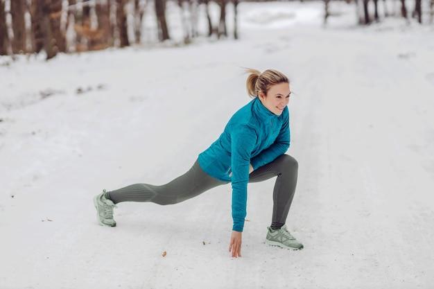 Sportlerin, die im winter in der natur auf schnee kauert und aufwärmübungen macht. natur, wald, winterfitness, gesunder lebensstil