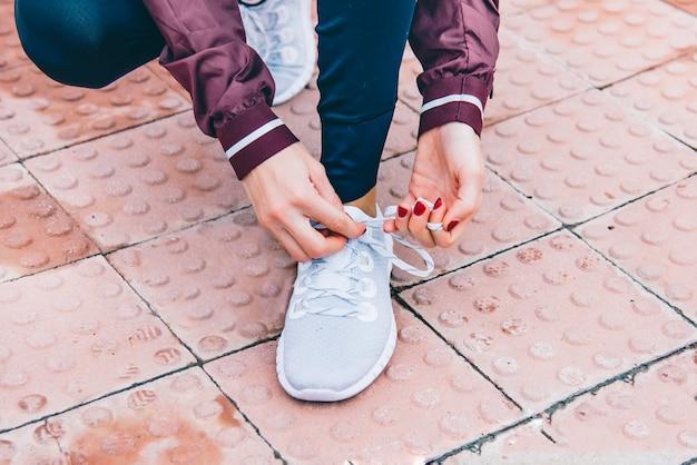 Sportlerin, die in der straße läuft, die ihren schuh bindet