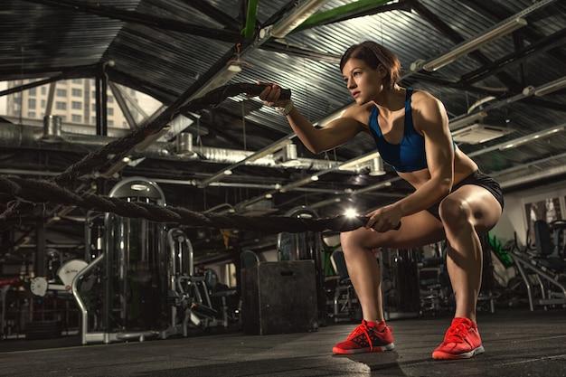 Sportlerin, die mit schweren seilen im fitnessstudio trainiert