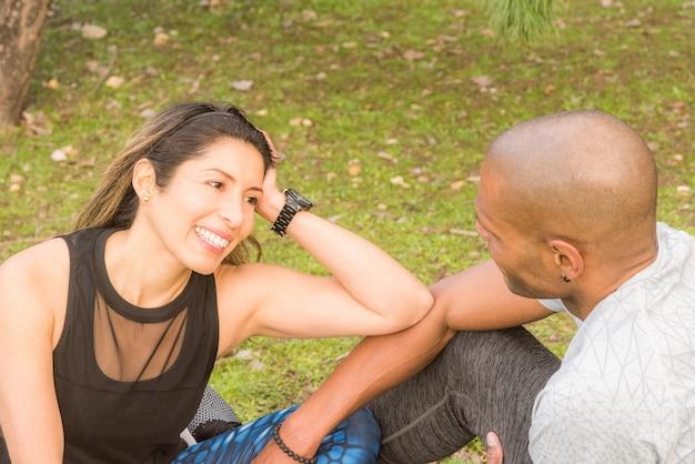 Sportlerin, die nach einem anstrengenden training mit ihrem sportfreund eine pause macht. multiethnische paare, die draußen trainieren.