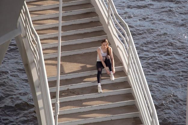 Sportlerin, die schnürsenkel an turnschuhen bindet, während sie auf stufen sitzt