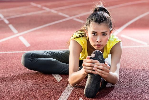 Sportlerin, die sich vor dem rennen auf die rennstrecke erstreckt