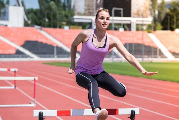Sportlerin, die über ein hindernis springt. laufen mit hürden. aktiver lebensstil