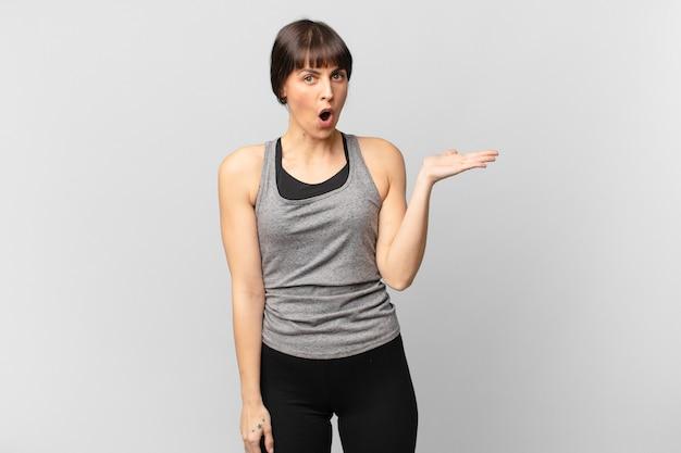 Sportlerin, die überrascht und schockiert aussieht, mit heruntergefallenem kiefer, die einen gegenstand mit offener hand an der seite hält