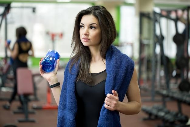 Sportlerin, die wasserflasche mit handtuch um den hals hält