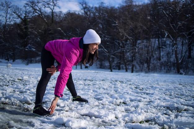 Sportlerin im winterkleidungstraining auf schnee.