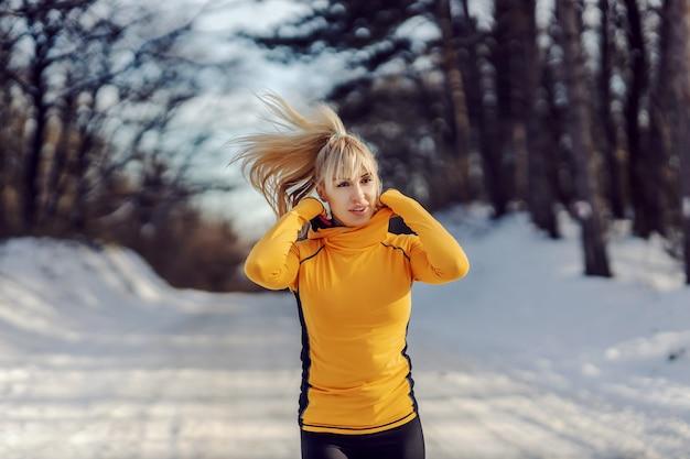 Sportlerin in form, die ihr sweatshirt beim gehen in der natur am verschneiten wintertag anpasst. sportbekleidung, gesundes leben, winterfitness