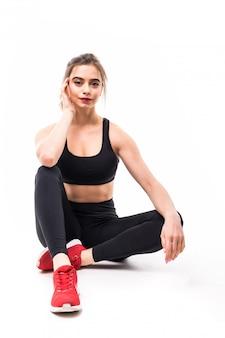 Sportlerin in schwarzer top-sportbekleidung sitzt isoliert auf dem boden in roten turnschuhen