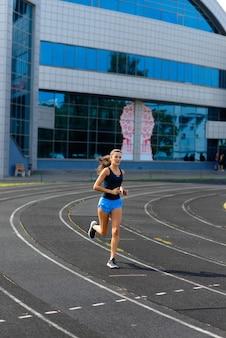 Sportlerin läuft auf sportlicher strecke und trainiert ihr cardio. frau, die für wettkampfrennen am sommeraußenstadion joggt.