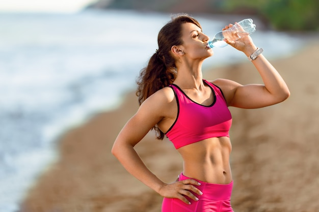 Sportlerin macht eine pause, sie trinkt wasser, läuft an einem heißen tag raus. frau läuft am strand bei sonnenuntergang