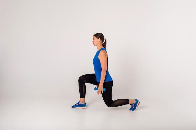 Sportlerin macht kniebeugenübungen mit hanteln auf einem weiß. seitenansicht.