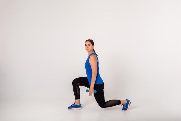 Sportlerin macht kniebeugenübungen mit hanteln und schaut in die kamera auf einem weiß