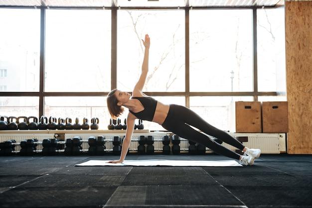 Sportlerin macht übungen auf matte im fitnessstudio