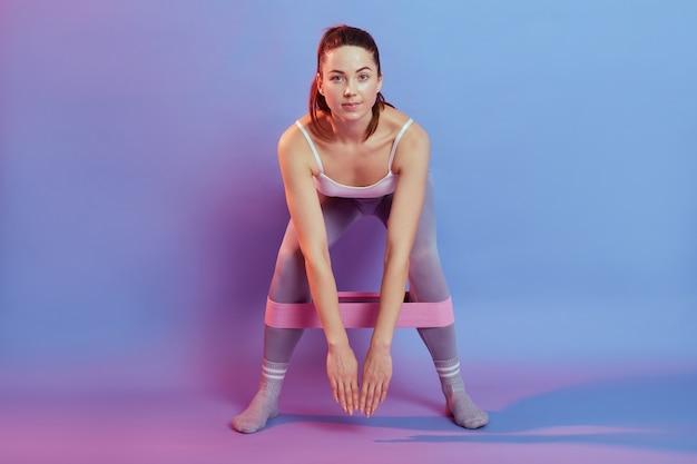 Sportlerin macht übungen mit widerstandsband und lehnt den körper nach vorne