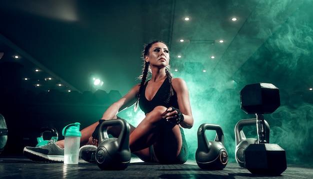 Sportlerin mit hanteln im fitnessstudio