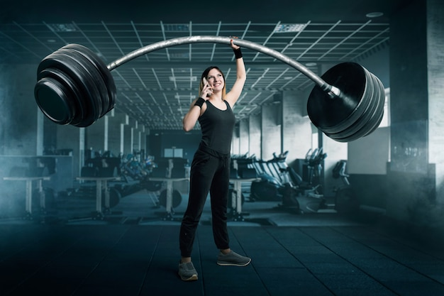 Sportlerin mit sehr großer langhantel, die telefonisch beim training in gim spricht. frau mit gewichten, gewichtheben sportkonzept