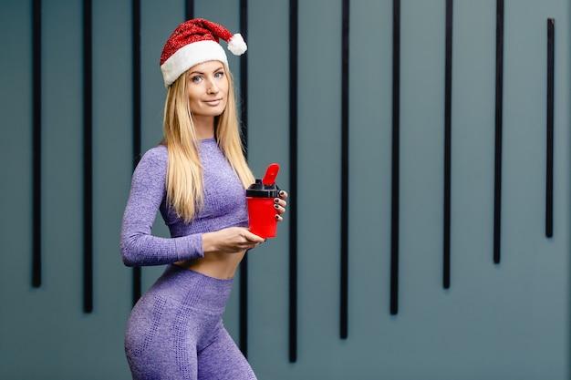 Sportlerin mit weihnachtsmütze hält wasserflasche