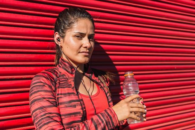 Sportlerin ruht auf einer roten wand mit einer wasserflasche und kopfhörern
