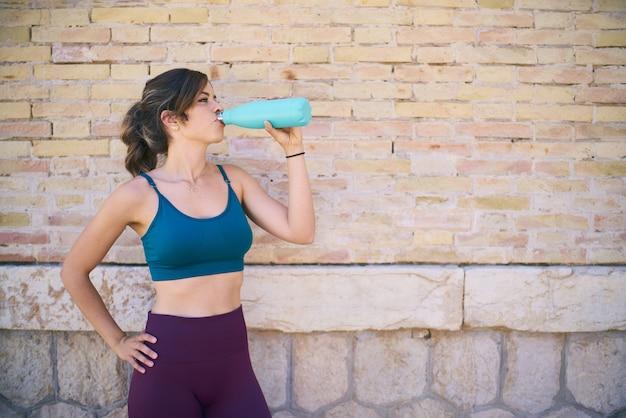 Sportlerin ruht sich an einer mauer gelehnt aus und trinkt aus einer flasche wasser gesundes lebensstilkonzept