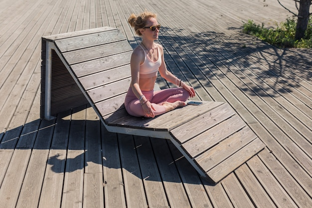 Sportlerin sitzt in yoga-meditationspose mit geschlossenen augen und im schneidersitz auf holzterrasse