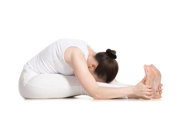 Sportlerin sitzt mit ihrem kopf zwischen ihre beine in yoga-kurs