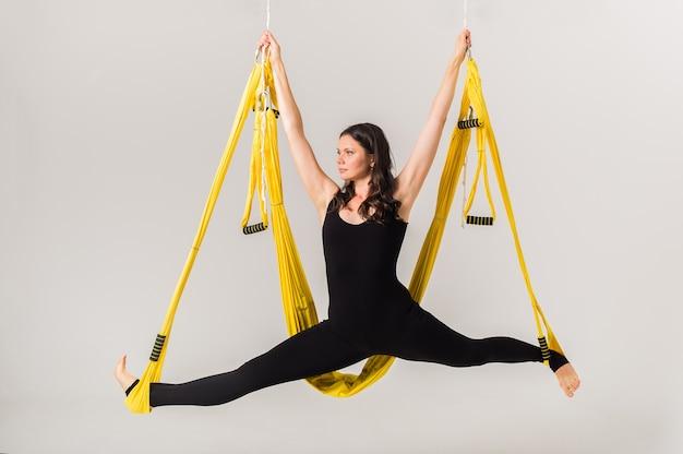 Sportlerin spaltet in einer gelben hängematte an einer weißen wand