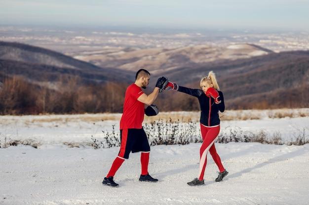Sportlerin sparring mit boxhandschuhen in der natur am verschneiten wintertag mit ihrem trainer. boxen, winter fitness, outdoor fitness
