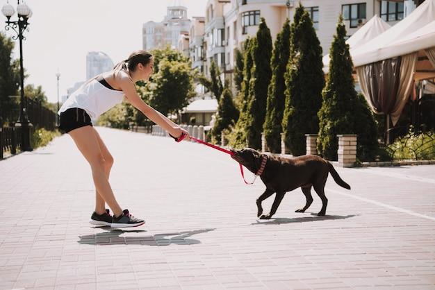 Sportlerin spielt mit hund auf der stadtpromenade