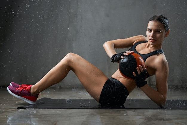 Sportlerin trainiert bauchmuskeln mit ball unter regen