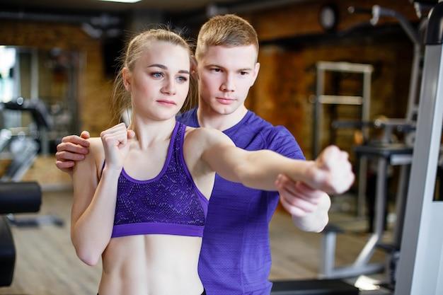 Sportlerin trainiert boxen mit trainer in der turnhalle