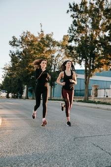 Sportlerinnen, die im sonnenlicht auf straße laufen