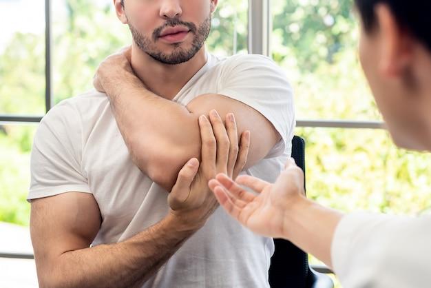 Sportlerpatient, der mit doktor über muskelschmerzen in der klinik sich berät