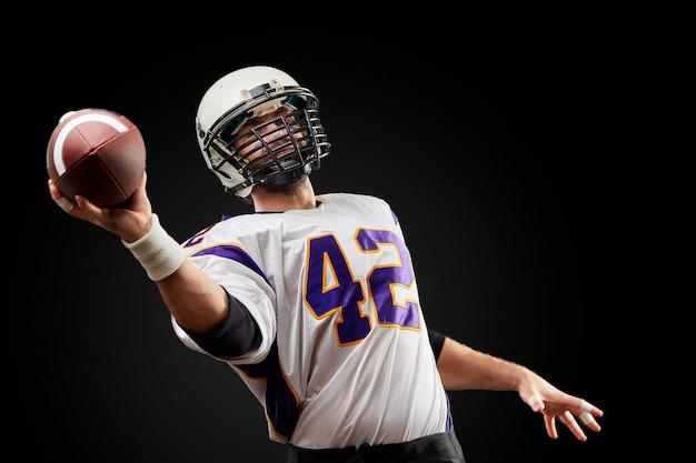 Sportlerspieler des amerikanischen fußballs auf schwarzem. sport .