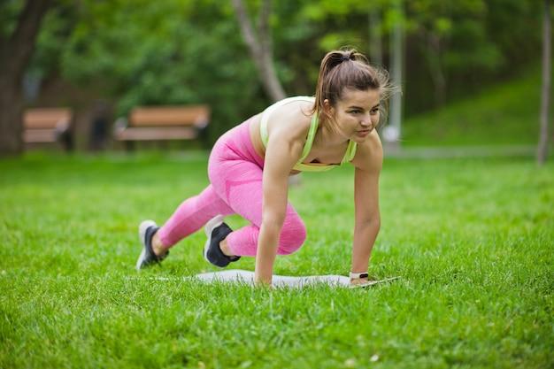 Sportlich fit frau, die aerobic-übung auf einer matte im park im freien macht