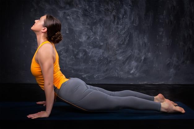 Sportlich fit yogini frau praktiziert yoga asana urdhva mukha svanas