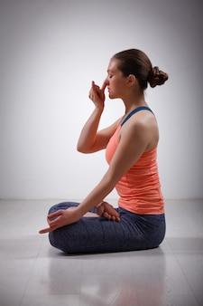Sportlich fit yogini frau praktiziert yoga pranayama atemkontrolle