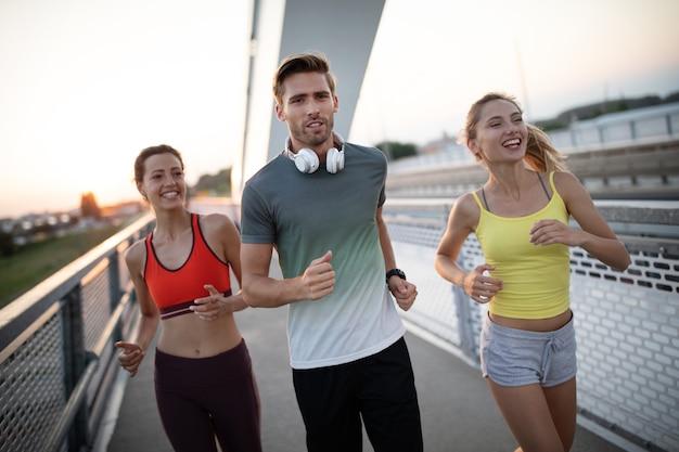 Sportlich fitte menschen, die zusammen draußen trainieren und joggen. sport, freunde, gesundheitskonzept