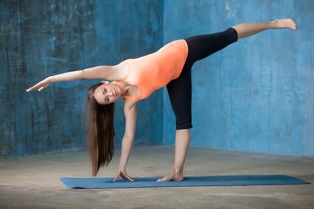 Sportlich schöne junge frau doing half moon pose