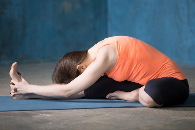 Sportlich schöne junge frau tun hamstring stretch übung