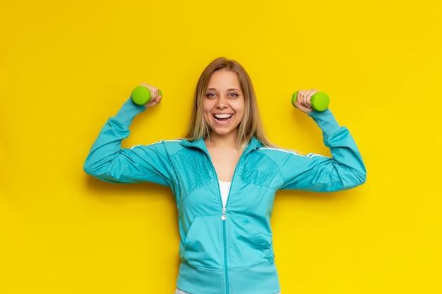 Sportlich schöne kaukasische athletin junge blonde frau in der türkisfarbenen sportjacke mit grünen hanteln lächelt und zeigt ihre stärke isoliert auf hellgelber wand wellness-sport