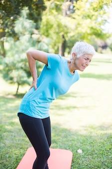 Sportliche ältere frau, die rückenschmerzen hat