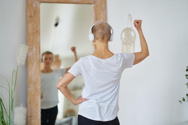 Sportliche ältere frau, die sich im spiegel bewundert, der vor einem großen spiegel in der wohnung steht