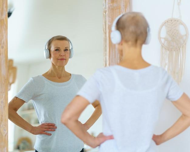 Sportliche ältere frau, die sich im spiegel bewundert