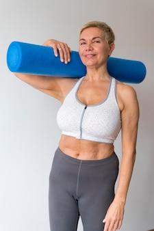 Sportliche ältere frau mit kurzen haaren, die fitnesszubehör halten
